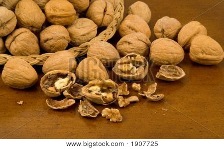 Whole Walnuts In Basket With Whole And Cracked Walnuts On Wood Table