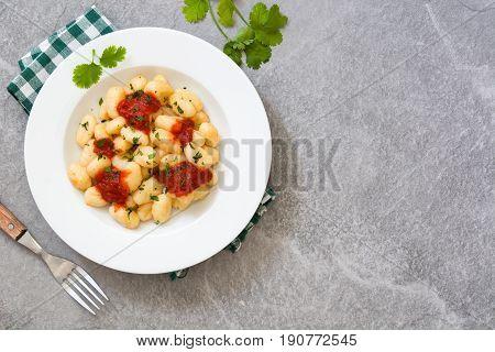 Gnocchi with tomato sauce on gray stone