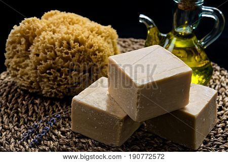 Handmade olive oil soaps together with a sea sponge, an oil bottle and a small branch of lavender