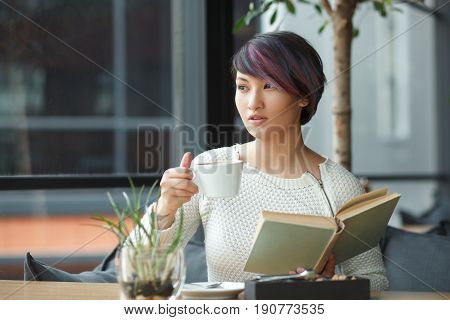 Young woman with short haircut holding book and cup of coffee looking away.