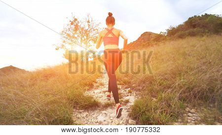 Young athletic woman running on mountain trail. Sunset Workout in Nature. Fit girl in pink top run. 4K
