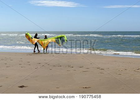 Castricum, The Netherlands - June 10, 2017: Two Young Women Handling A Kite While Standing On The Be
