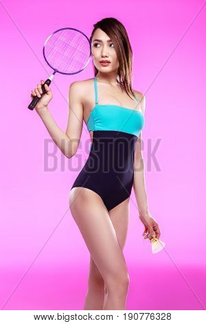 Young Asian Woman In Swimsuit Holding Badminton Racquet With Shuttlecock And Looking Away