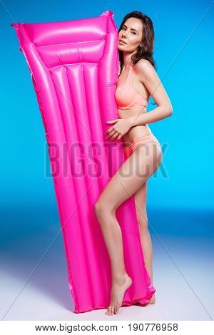 Beautiful Brunette Young Woman In Swimsuit Posing With Air Mattress And Looking At Camera