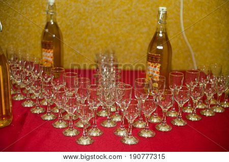 Empty champagne flutes surround a bottles of alcohol standing on the red table