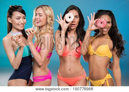 Young Multiethnic Women In Swimsuits Holding Sweet Doughnuts