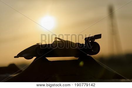 Outline of historic single-seater with sunset in background