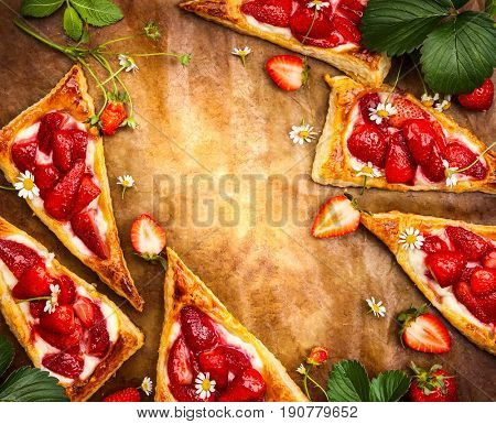 Delicious idea for summer dessert: Puff pastry tart with strawberry and ricotta cheese in triangles shaped. Top view