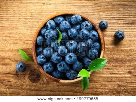 Fresh blueberry with drops of water on wooden background. Top view. Concept of healthy and dieting eating