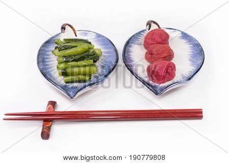 Japanese cuisine , Traditional Japanese Umeboshi  (plum pickle) and Pickle of traditional vegetables with Chopsticks or  equipment for eating is placed on white background.