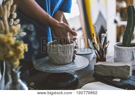 Male artisan in his workshop carefully molds sculpture with dirty hands puts in experience and craft to creat artistic piece of clay