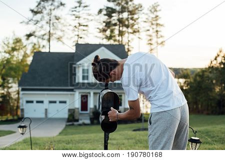 Young home owner checks on new letters and bills in his american typical mailbox in workout clothing sweatpants on sunny warm summer evening