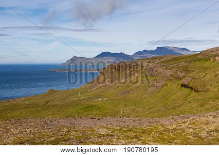 Icelandic Landscape With Green Hills On The Foreground And High Cliffs And Atlantic Ocean On The Bac