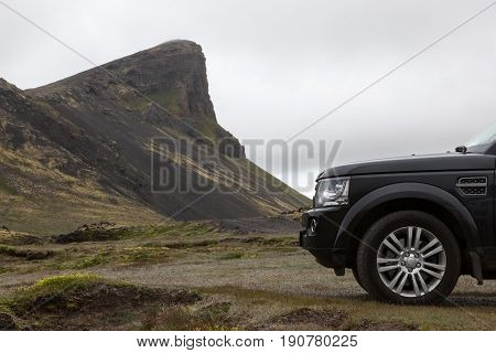 Traveling By Off Road 4Wd Car In Iceland. Black Car Parked On The Grass In Iceland Landscape. Beauti