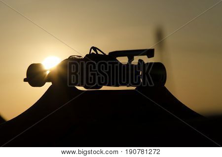 Outline of classic single-seater with sunset in background