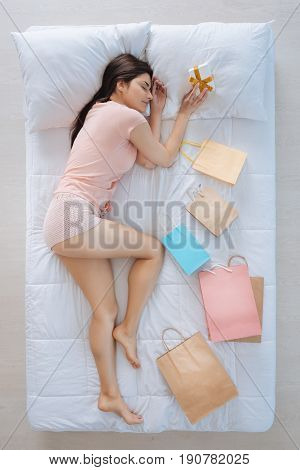 Present for me. Happy cheerful cute woman lying on the bed and holding a present box while being surrounded by shopping bags