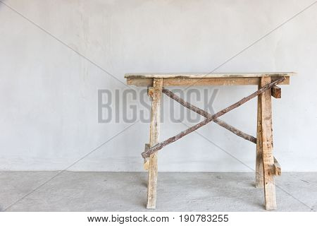wood scaffolding in room with walls plastered into the background.