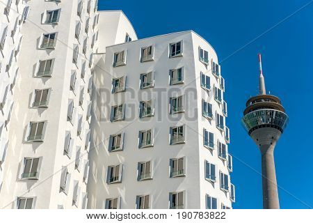 Closeup view of Frank Gehry's famous modern building at Neuer Zollhof and Rheinturm tower in Dusseldorf, Germany.