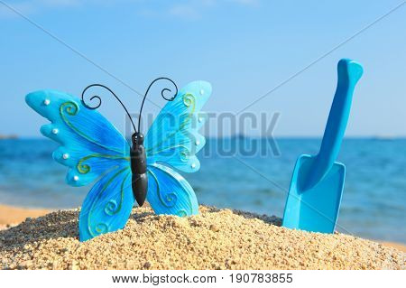 Blue butterfly and shovel at the beach