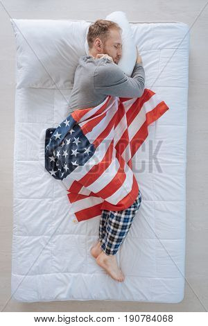 Patriotic feelings. Pleasant good looking adult man lying on his side and sleeping while being wrapped in the US flag