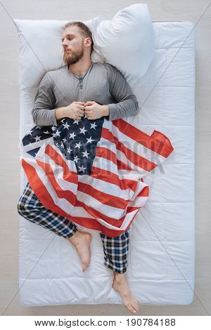 My homeland. Handsome nice American citizen lying on his back and holding the US flag while being asleep