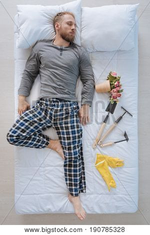 Gardening design. Handsome nice male gardener lying on the bed and resting while dreaming about his job