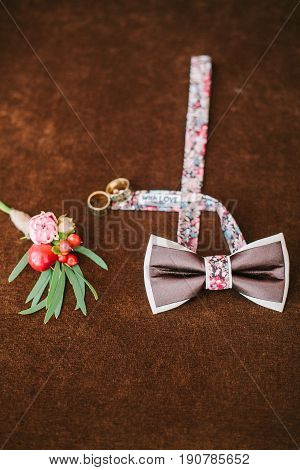 groom's accessories for a wedding. top view on a bow tie, buttonhole and rings on a brown velvet background. preparation for a wedding. set groom concept.