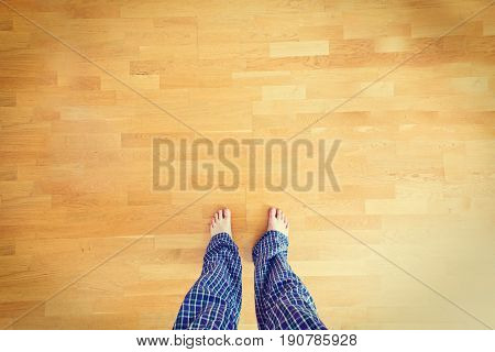 Legs in pajamas. Bare feet on a wooden floor.