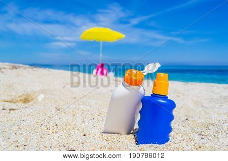 detail of suntan lotion bottles on the sand