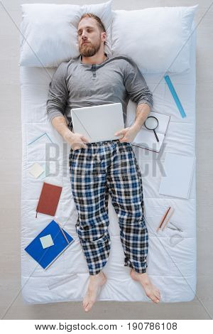Office worker. Good looking nice pleasant man lying on the bed and holding a tablet while dreaming of his work