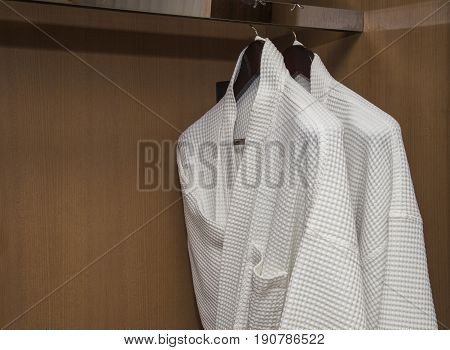 White bathrobes with wooden hangers in wardrobe