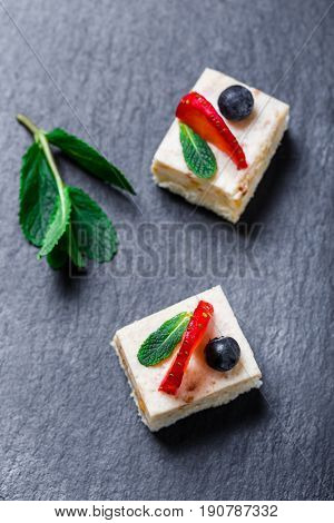 Mini cakes with strawberry and blueberry on stone slate background close up. Homemade baking. Flat lay top view