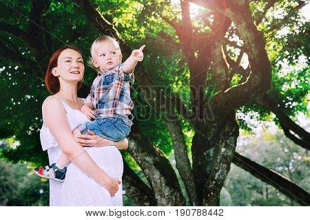 Pregnant woman with child outdoors. Mother and son on nature in park. Little child boy is sitting on belly of his mother who pregnant for second time. Pregnancy new life family parenthood concept.
