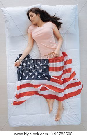Patriotic feelings. Nice attractive pleasant woman lying in the bed and holding the US flag while showing her patriotic feelings