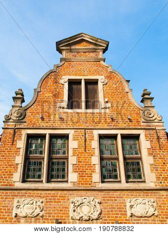 Ancient brick house gable with ornamental windows. Architecture of Bruges, Flanders, Belgium.