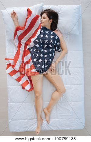 President of the USA. Joyful pleasant nice woman lying in the bed and being the US president while having a patriotic dream