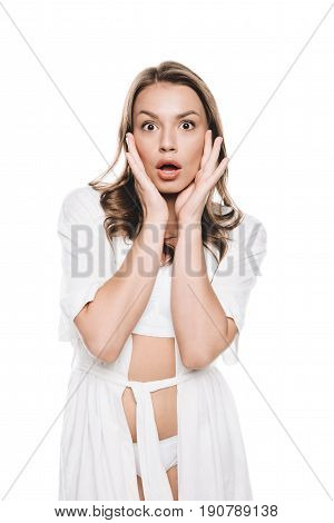 Portrait of woman in white robe gesturing with shocked expression looking at camera isolated on white