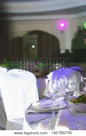 Festively served tables for celebrations and events. Clean utensils, plates and glasses for the drinks prepared for guests. Catering at the wedding and celebrations. Soft focus and beautiful bokeh.