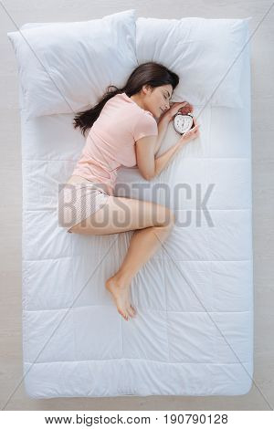 Useful invention. Attractive young brunette woman sleeping and holding an alarm clock while wanting to wake up in time