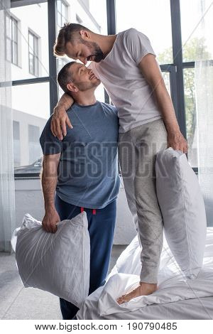 Happy Homosexual Couple Standing Embracing In Bedroom After Pillow Fight