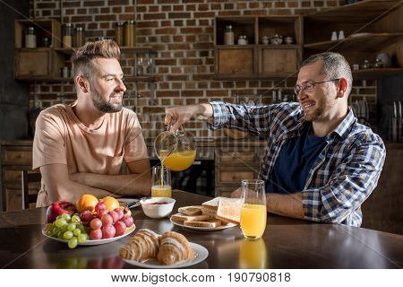 Happy Homosexual Couple Having Breakfast And Talking At Home