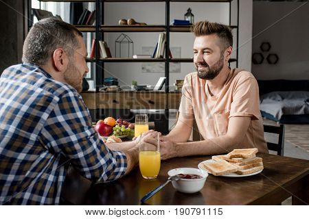 Homosexual Couple Holding Hands And Looking At Each Other During Breakfast