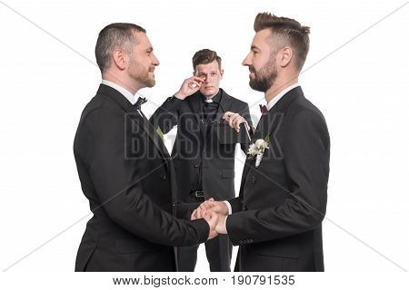 Homosexual Couple Pronouncing Vows And Holding Hands At Wedding Ceremony