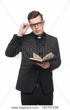 Young Priest In Black Suit Reading Scripture Book And Looking At Camera Isolated On White