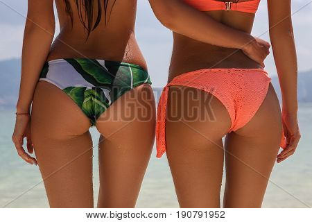 Two sexy womans buttocks with beautiful clear water background. concept about vacations body care summer nature and people. Close up shoot poster