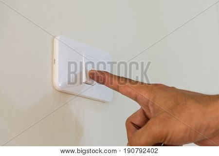 Men's fingers are extended to open the light switch on the wall.