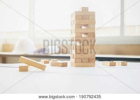 Planning risk and strategy in construction site or office. Engineering gambling placing wooden block on a tower.