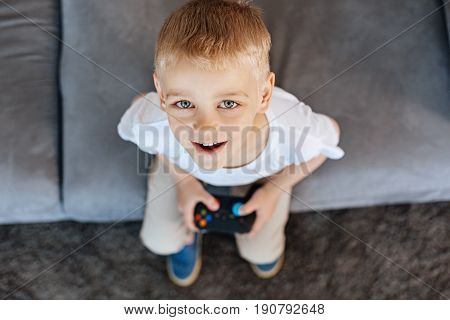 Adorable boy. Enthusiastic cute clever boy sitting on a couch and playing video games while holding a special controller in his hands