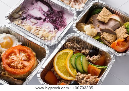 Healthy restaurant food background. Eating right concept. Fresh diet daily meals delivery. Fitness nutrition, vegetables, meat and dessert in foil boxes
