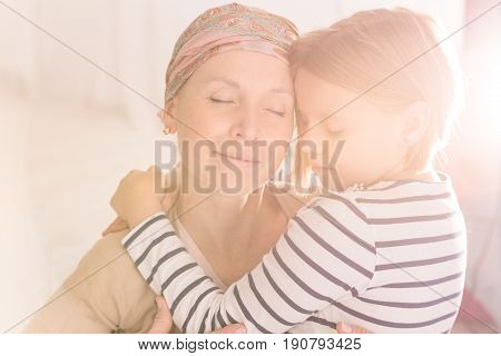 Fondly hugging of mother with cancer and child